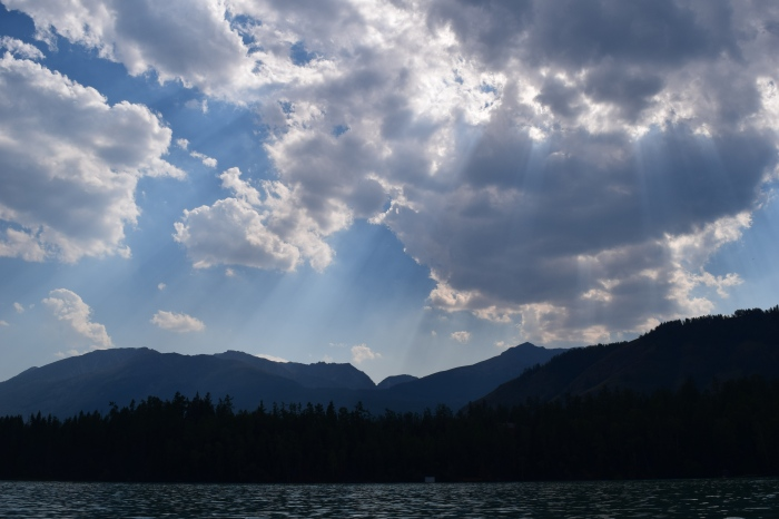 amazing rays of afternoon sun pierced through the clouds captured during a river cruise on Kanas Lake